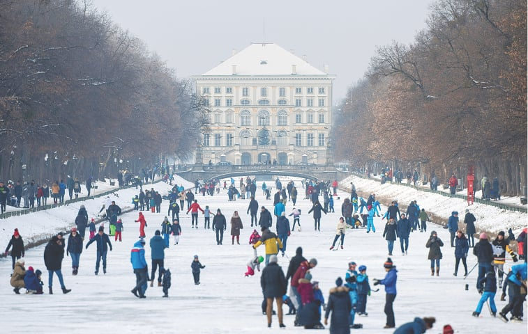 MUNICH: Excursionists cavort on a frozen canal in front of Nymphenburg Palace on Sunday, one day before most parts of Germany come under lockdown.—AP
