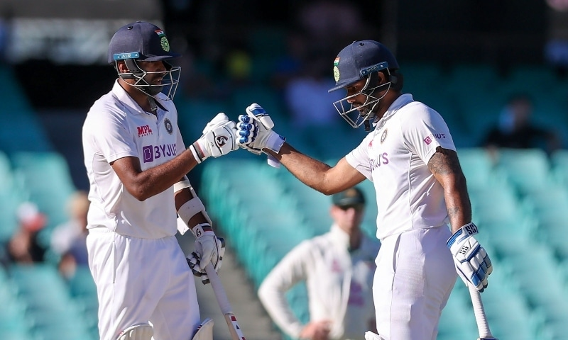 India's Ravichandran Ashwin (L) and teammate Hanuma Vihari touch gloves during the fifth day of the third cricket Test match between Australia and India at the Sydney Cricket Ground (SCG) in Sydney on January 11. — AFP