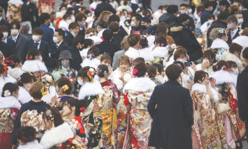 """KAWASAKI (Japan): Twenty-year-old men and women, dressed in kimonos, gather outside an arena during a """"coming-of-age day"""" ceremony on Monday.—AFP"""