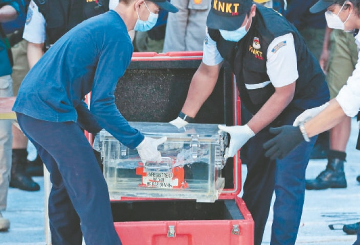JAKARTA: Members of Indonesia's transportation safety committee place a box containing the flight data recorder of Sriwijaya Air flight into a container after a press conference on Tuesday. The recorder was retrieved from the Java Sea, where the passenger jet crashed on Saturday.—AP