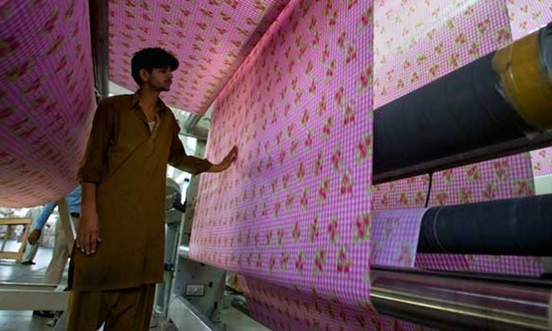 A worker examines fabric at a textile factory — AP/File