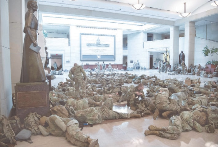 WASHINGTON: Members of the National Guard take rest in the Capitol's visitors centre.—AFP