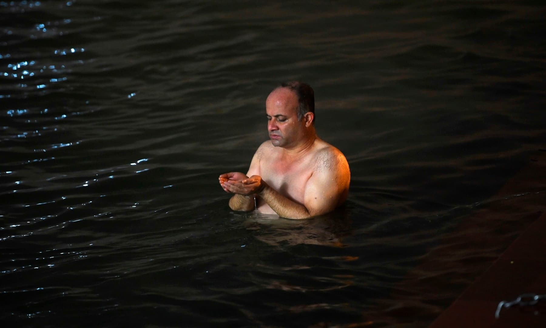 A Hindu devotee offers prayers as he takes a holy dip in the waters of river Ganges during Makar Sankranti, on the first day of the religious Kumbh Mela festival in Haridwar on January 14. — AFP