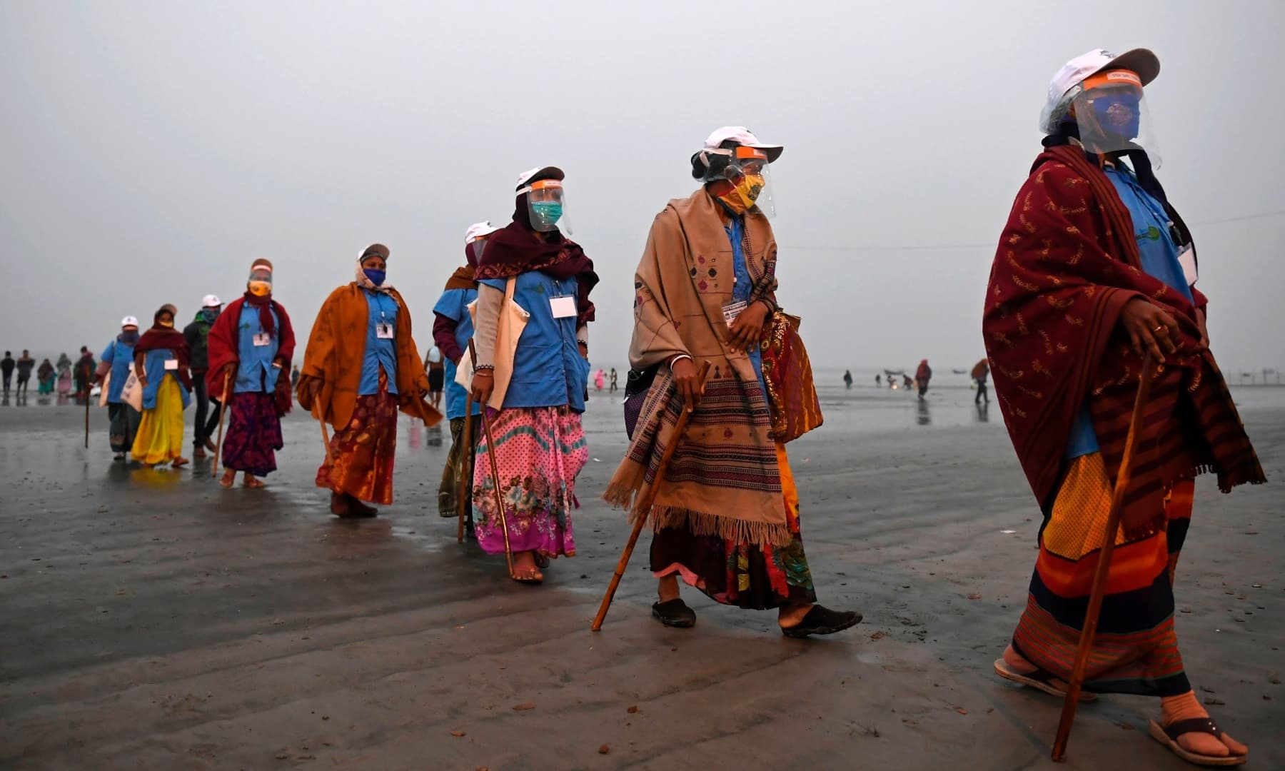 Members of local village panchayat wearing face shields and masks inspect the sanitisation on the beach as a preventive measure against Covid-19 at the confluence of the Ganges and the Bay of Bengal at Sagar Island, south of Kolkata. — AFP