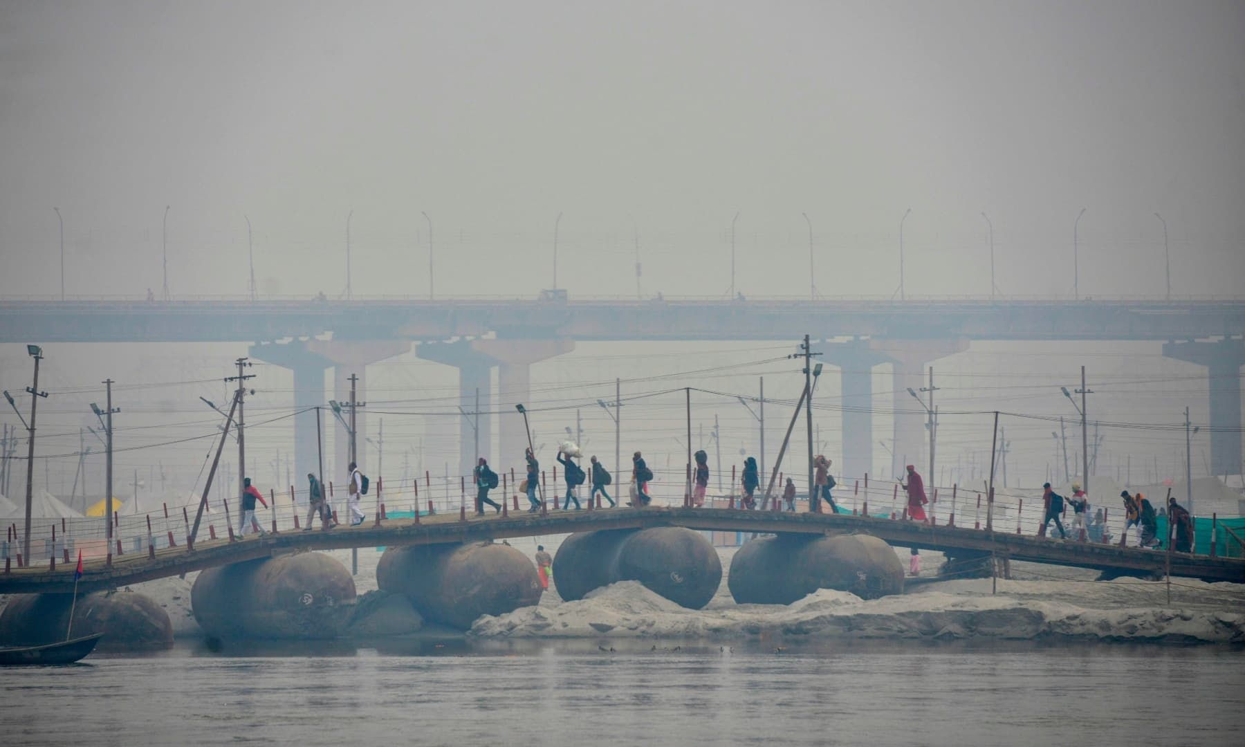 Hindu devotees walk across a newly constructed temporary pontoon bridge on the banks of Sangam, the confluence of rivers Ganges, Yamuna and the mythical Saraswati, on the occasion of Makar Sankranti, in Allahabad on January 14. — AFP