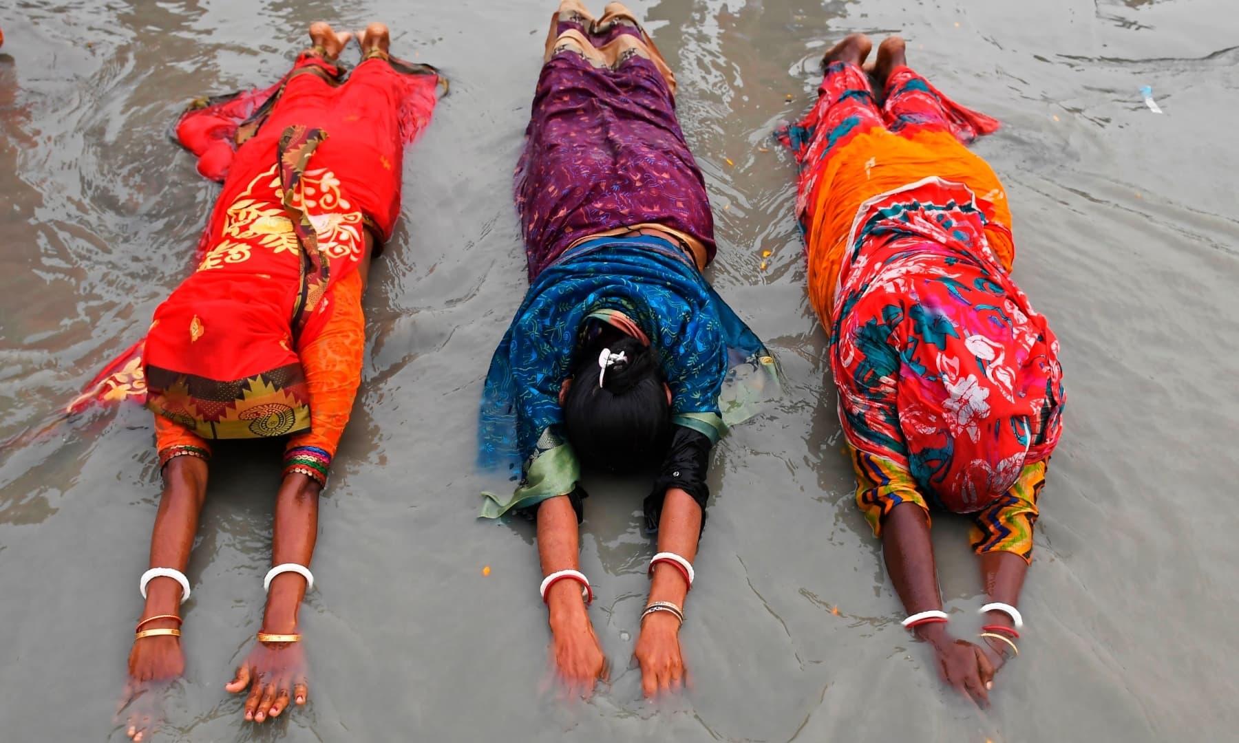 Hindu pilgrims offer prayers at the confluence of the Ganges and the Bay of Bengal during the Gangasagar Mela on the occasion of Makar Sankranti, at Sagar Island south of Kolkata on January 14. — AFP
