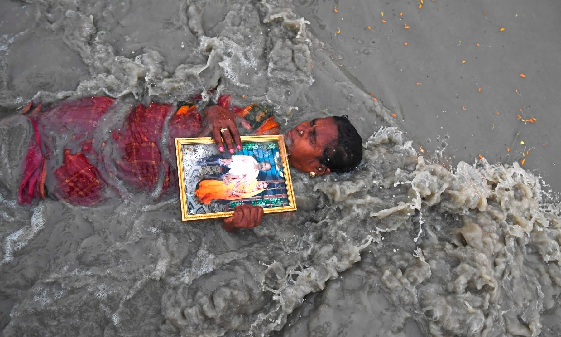 A Hindu pilgrim holds a picture of herself with her late husband as she takes a holy dip at the confluence of the Ganges and the Bay of Bengal during the Gangasagar Mela on the occasion of Makar Sankranti, at Sagar Island, south of Kolkata. — AFP
