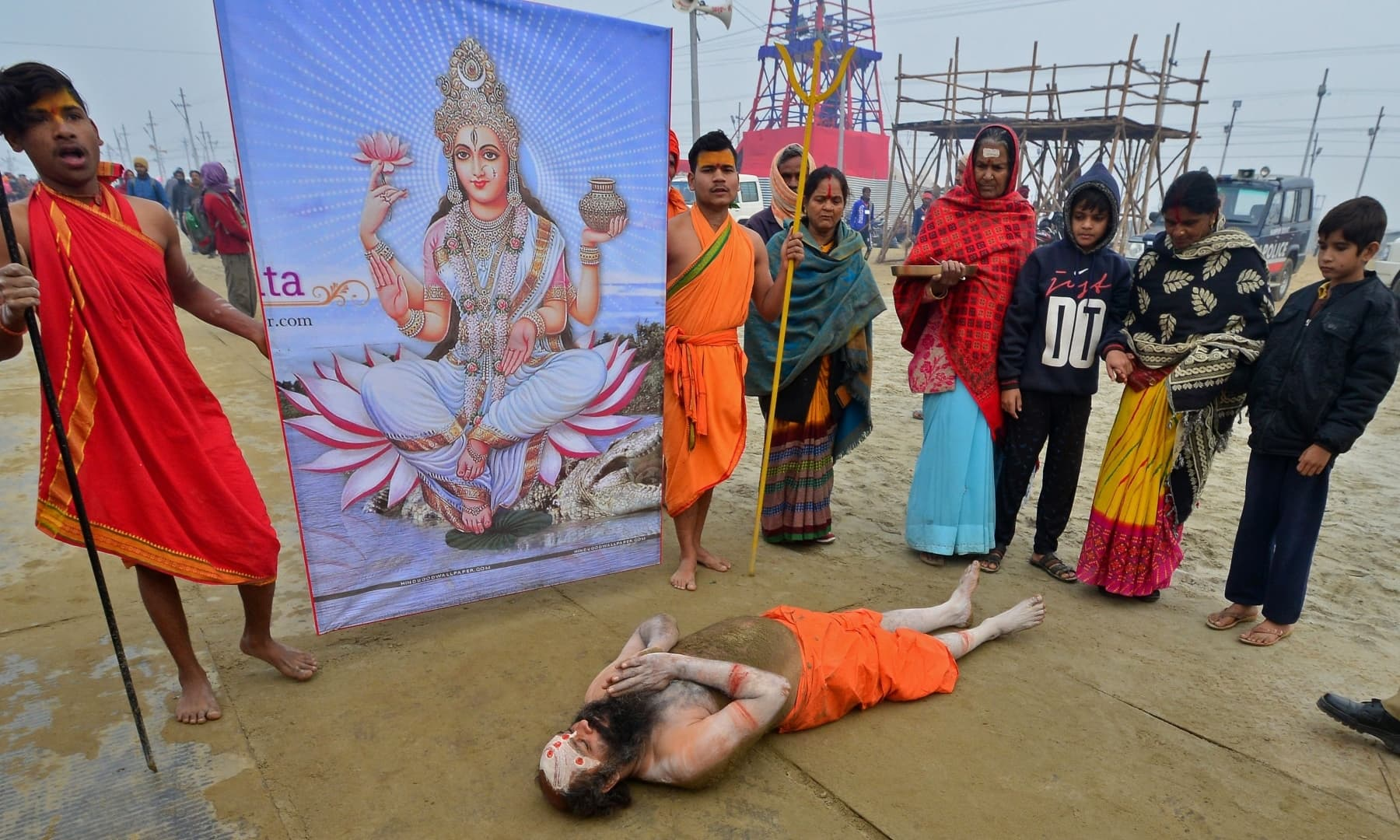 A Sadhu or a Hindu holy man performs a ritual as he arrives to take a holy dip at Sangam, the confluence of rivers Ganges, Yamuna and the mythical Saraswati, on the occasion of Makar Sankranti in Allahabad on January 14, — AFP