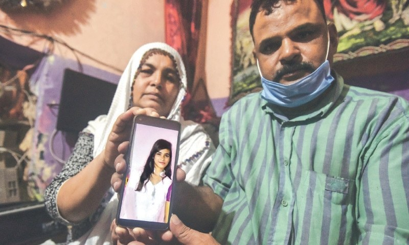 In this file photo, Arzoo's parents hold up her picture.—Fahim Siddiqi/White Star