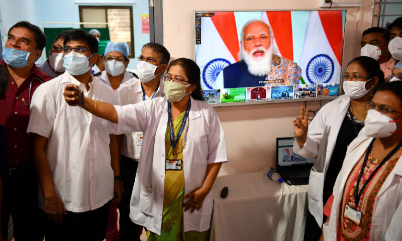 Doctors from the Rajawadi Hospital pose for a selfie as a television broadcasts a live address by India's Prime Minister Narendra Modi before the start of the Covid-19 vaccination drive in Mumbai on Saturday. — AFP