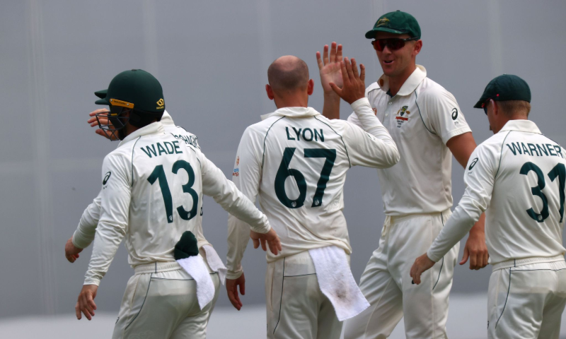 Australia's Nathan Lyon(C) celebrates his wicket of India's batsman Rohit Sharma with teammates on day two of the fourth cricket Test match between Australia and India at the Gabba in Brisbane on Jan 16, 2021. — AFP