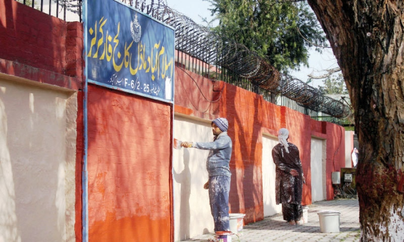 Painters give a fresh look to the wall of Islamabad Model College for Girls, F-6, on Saturday. Classes for students of grades 9 to 12 will resume from Monday. — Online