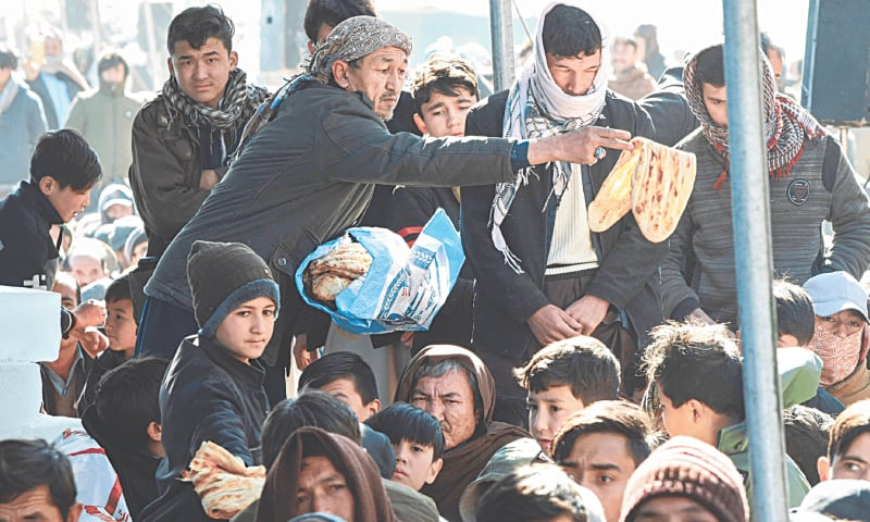 A man gives naans to mourners during the sit-in on the outskirts of Quetta | AFP