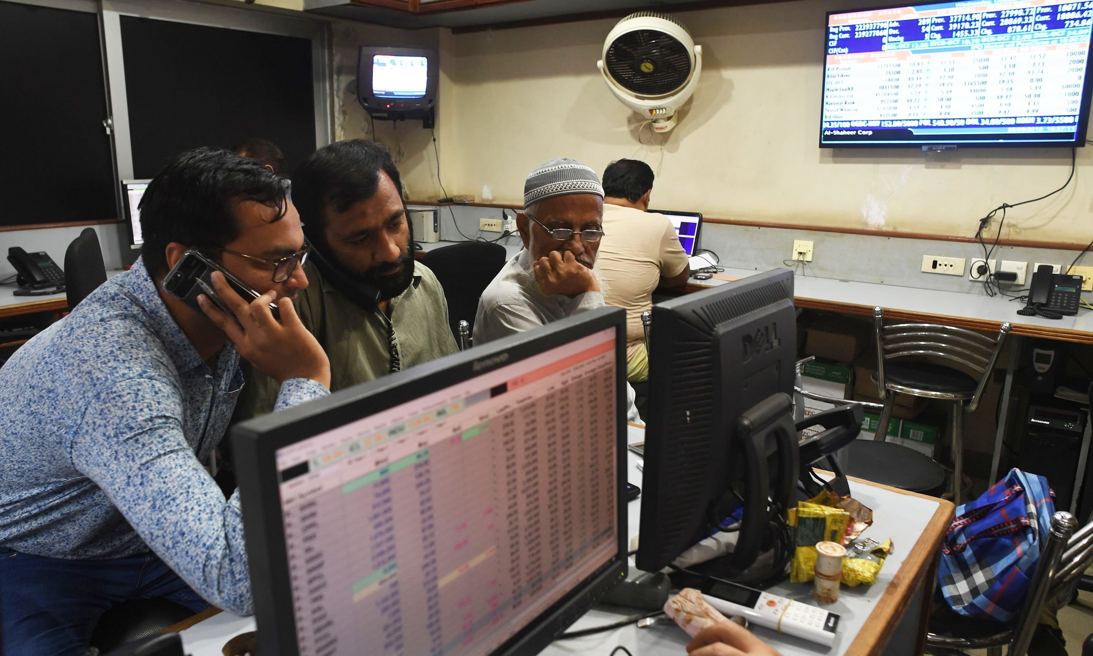In this file photo, stockbrokers watch the latest share prices on their monitors during a trading session at the Pakistan Stock Exchange (PSX) in Karachi. — AFP/File