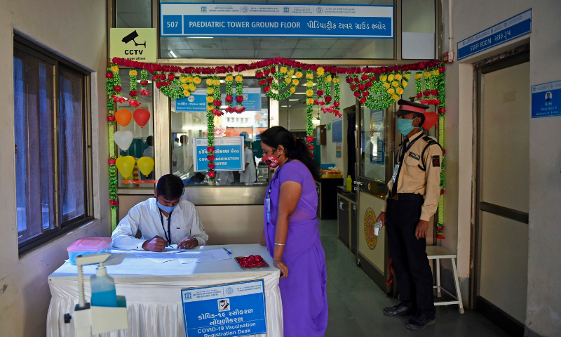 Medical workers wait to be inoculated with a Covid-19 vaccine at a hospital in Allahabad on Saturday. — AFP