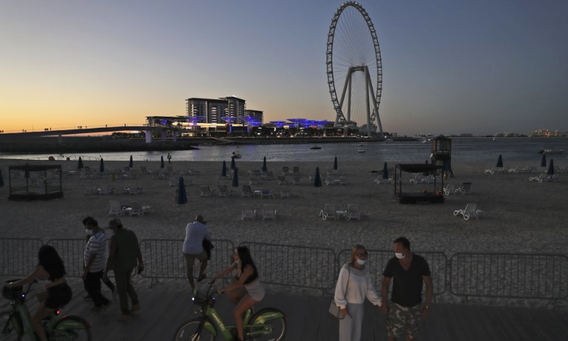 Tourists and residents enjoy the sunset at the Jumeirah Beach Residence, in Dubai, United Arab Emirates, on January 12, 2021. — AP