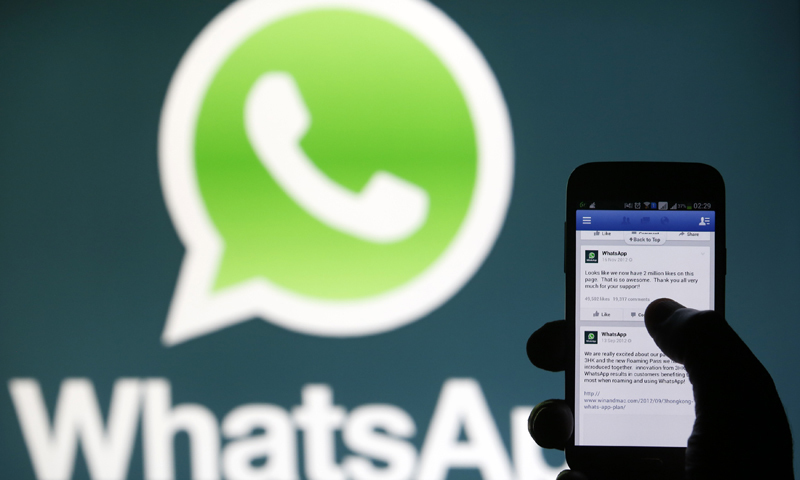 A Whatsapp App logo is seen behind a Samsung Galaxy S4 phone that is logged on to Facebook in the central Bosnian town of Zenica on February 20, 2014. — Reuters/File