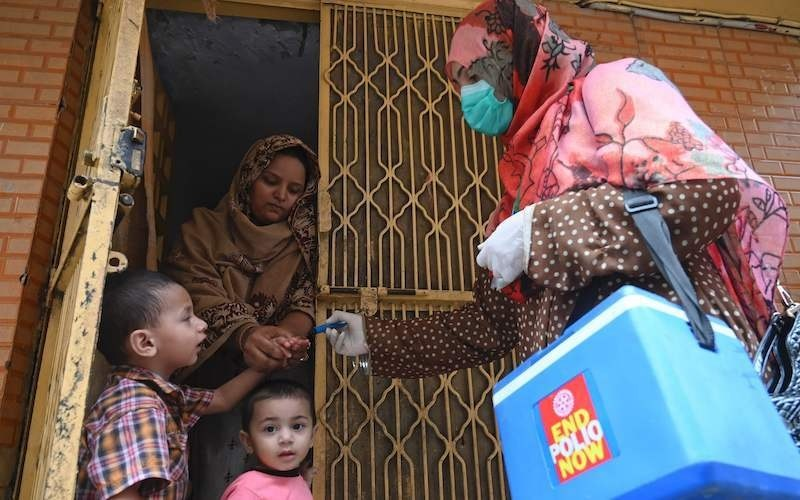 A health worker (R) marks the finger of a child after administering polio vaccine drops during a door-to-door campaign in Lahore on July 20, 2020. — AFP/File