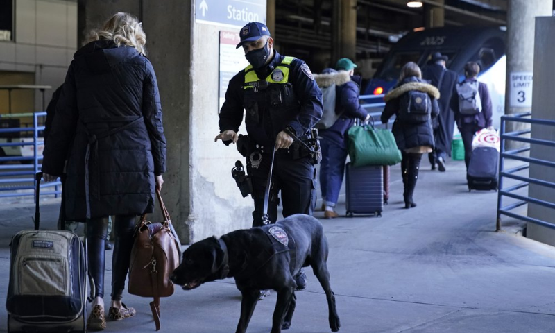An Amtrak K9 officer and his dog check passengers before they board an Amtrak train before its departure from Union Station as security is heightened ahead of President-elect Joe Biden's inauguration ceremony. — AP