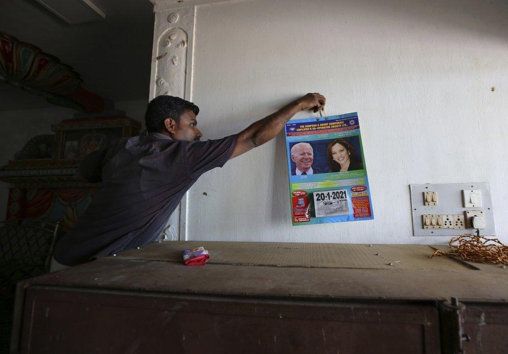 A villager hangs a calendar featuring photographs of US President Joe Biden and Vice President Kamala Harris inside a wedding hall in Thulasendrapuram.