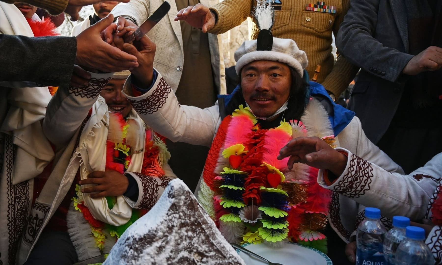 Nepal's climbers Nirmal Purja (L) and Mingma Sherpa (R) cut a cake upon their arrival after becoming the first to summit Pakistan's K2 in winter, during a ceremony at Shigar district in Gilgit-Baltistan, Jan 20, 2021. — AFP