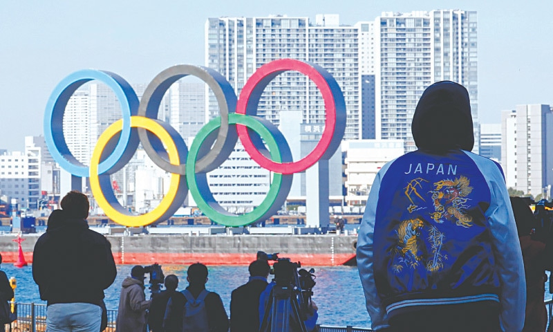 BYSTANDERS watch as giant Olympic rings are reinstalled at the waterfront area at Odaiba Marine Park, after they were temporarily taken down in August for maintenance amid coronavirus disease outbreak.—Reuters