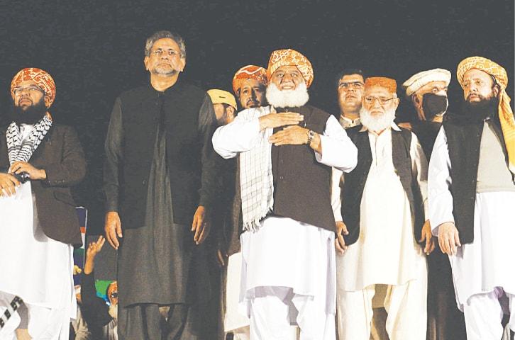 JUI-F chief Maulana Fazlur Rahman flashes a smile at the rally accompanied on stage by Shahid Khaqan Abbasi and other leaders on Thursday.—Shakil Adil/White Star