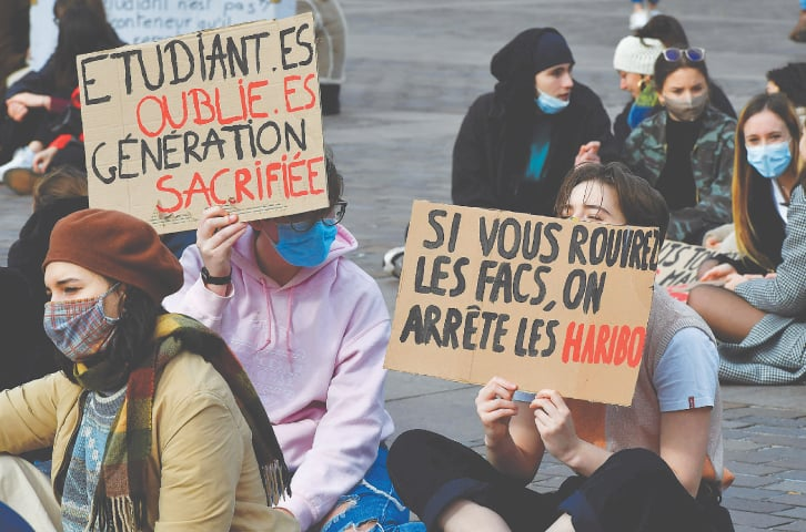 """TOULOUSE (France): Students of the University of Toulouse hold placards reading """"Forgotten students, sacrificed generation"""" during a demonstration to demand the resumption of on-site classes.—AFP"""