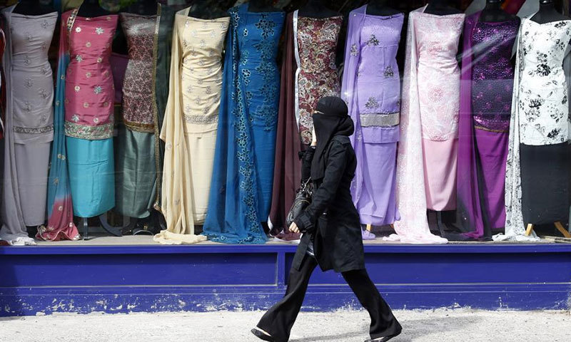 A woman walks past a clothes shop in the Sparkbrook area of Birmingham, central England. — Reuters/ File