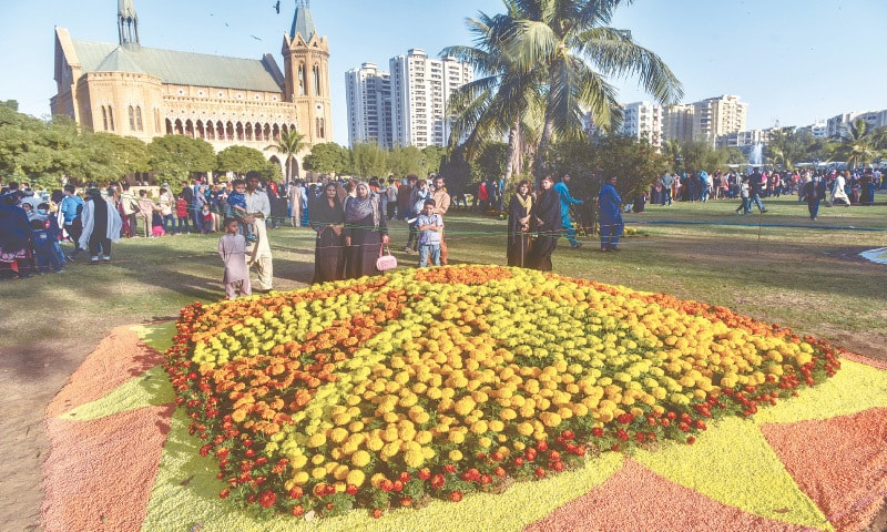 PEOPLE admire a display of marigolds at the Frere Hall lawns on Friday.—Fahim Siddiqi/White Star