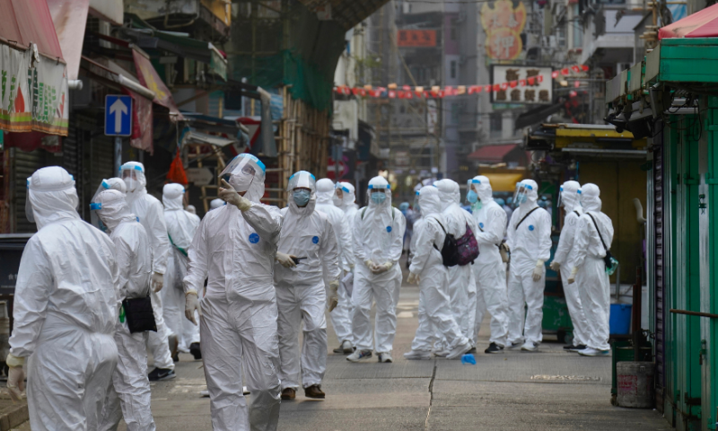 Government investigators wearing protective suits, gather in the Yau Ma Tei area, in Hong Kong on Saturday. — AP