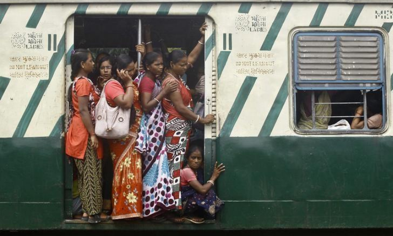 Female commuters stand at an open doorway of a suburban train during the morning rush hour in Kolkata. — Reuters/File
