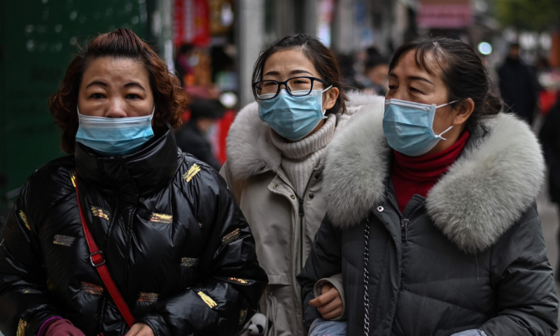 Pedestrians wearing face masks as a preventive measure against Covid-19 walk on a street in Wuhan, China's central Hubei province on January 22. — AFP