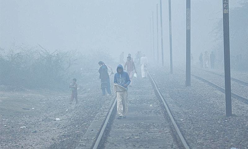 In this file photo, people cross the railway track in the Walton area of Lahore during foggy weather. — Online