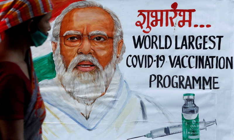 A woman walks past a painting of Indian Prime Minister Narendra Modi a day before the inauguration of the Covid-19 vaccination drive on a street in Mumbai, India, January 15, 2021. — Reuters