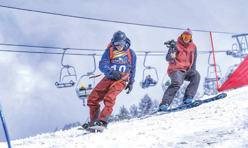 A cameraman films a participant on the final day of snowboarding championship in Swat. — Dawn