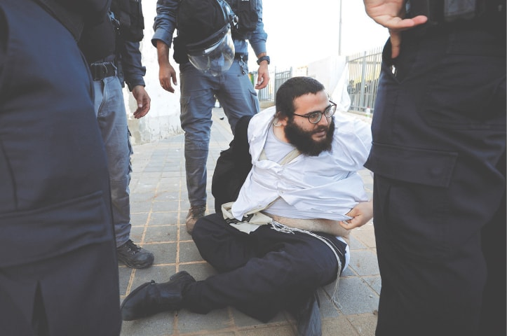 ASHDOD: Police detain an ultra-Orthodox Jew during the protest.—Reuters