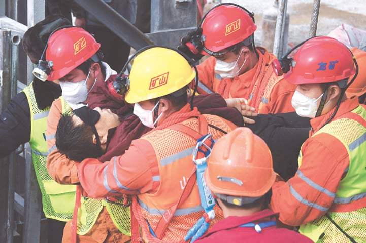 THIS photo released by Xinhua News Agency shows relief workers carrying a rescued miner to an ambulance in Qixia City, in China's Shandong province, on Sunday.—AP