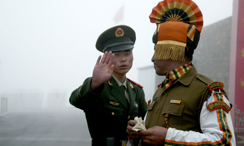 In this file photo taken on July 10, 2008 a Chinese soldier gestures as he stands near an Indian soldier on the Chinese side of the ancient Nathu La border crossing between India and China. — AFP
