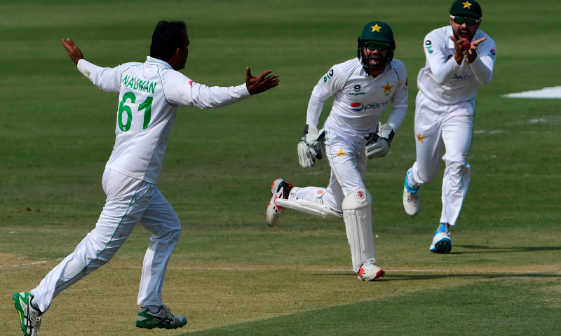 Pakistan's captain Babar Azam (R), wicketkeeper Mohammad Rizwan (C) and Nauman Ali celebrate the dismissal of South Africa's Dean Elgar during the first day of the first cricket Test match between Pakistan and South Africa at the National Stadium in Karachi on Tuesday. — AFP