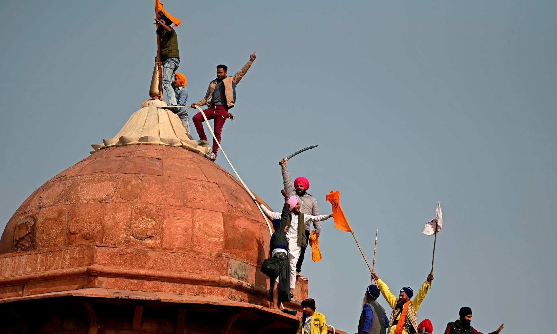 Protesters climb on a dome at the ramparts of the Red Fort as farmers continue to demonstrate against the Indian government's recent agricultural reforms in New Delhi on January 26. — AFP