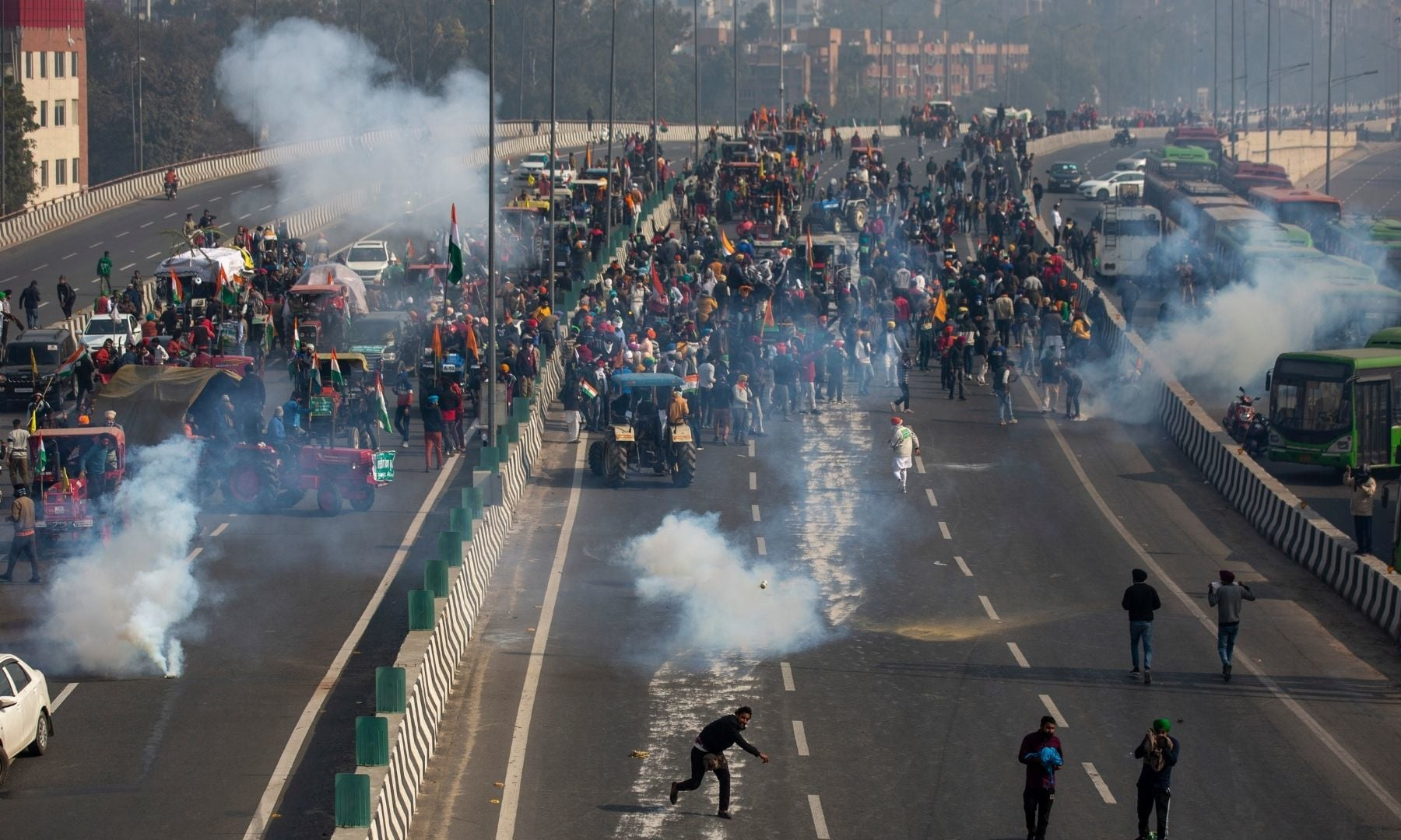 A protesting farmer hurls back a tear gas shell towards police as they march to the capital breaking police barricades during India's Republic Day celebrations in New Delhi on Jan 26. — AP