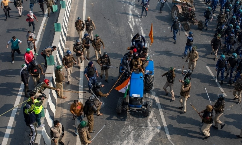 Indian policemen beat farmers driving a tractor after protesting farmers and policemen clash during India's Republic Day celebrations in New Delhi, Jan 26. — AP