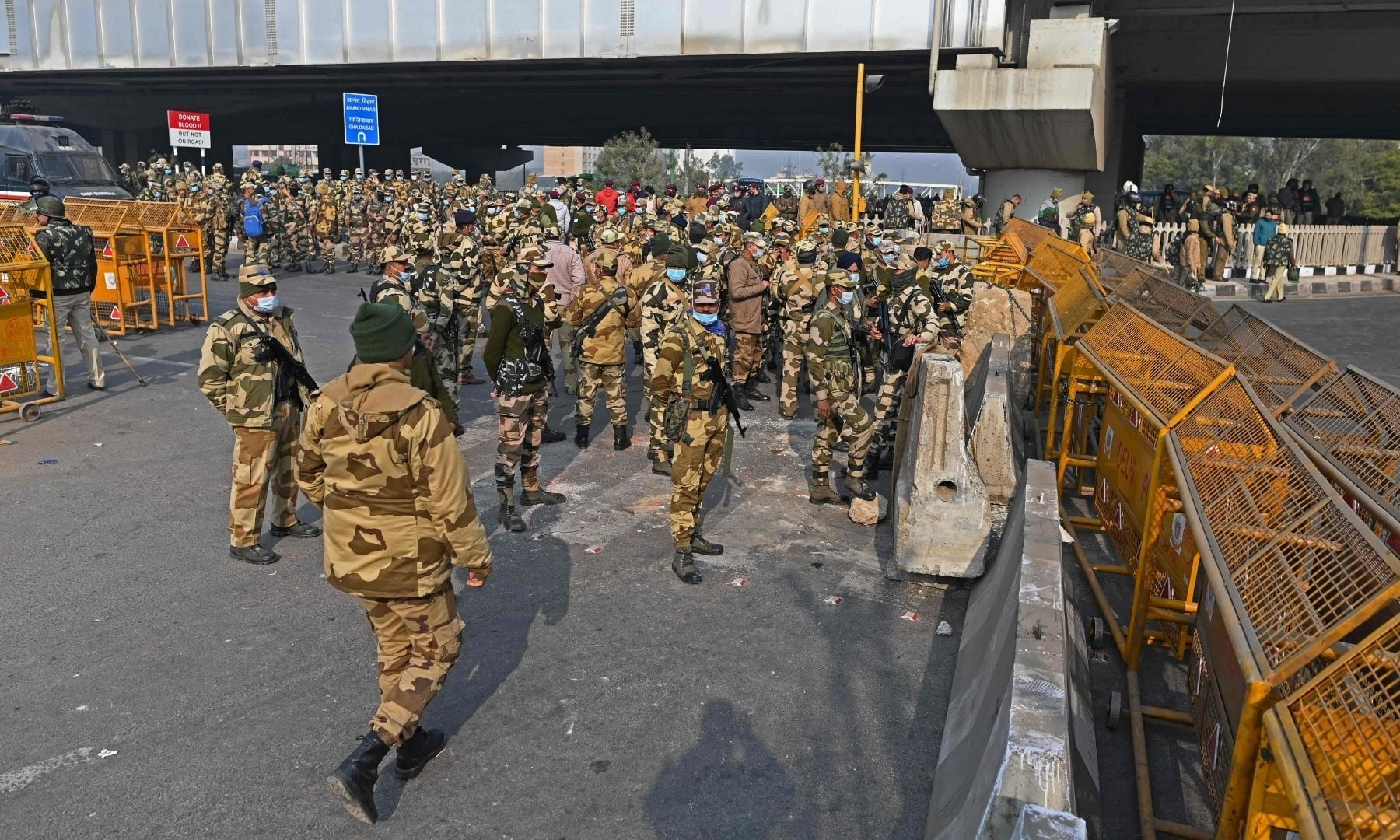 Security personnel stand guard along a blocked highway at the Delhi-Uttar Pradesh state border in Ghazipur on Jan 26. — AFP