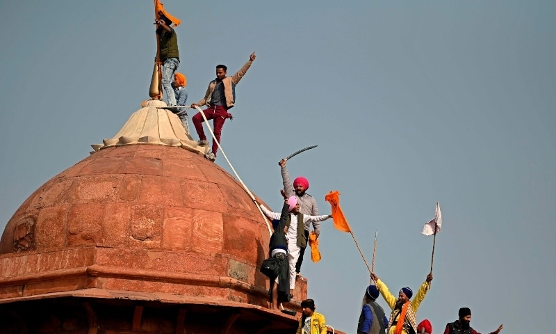 Protesters climb on a dome at the ramparts of the Red Fort during the protest in New Delhi on January 26. — AFP
