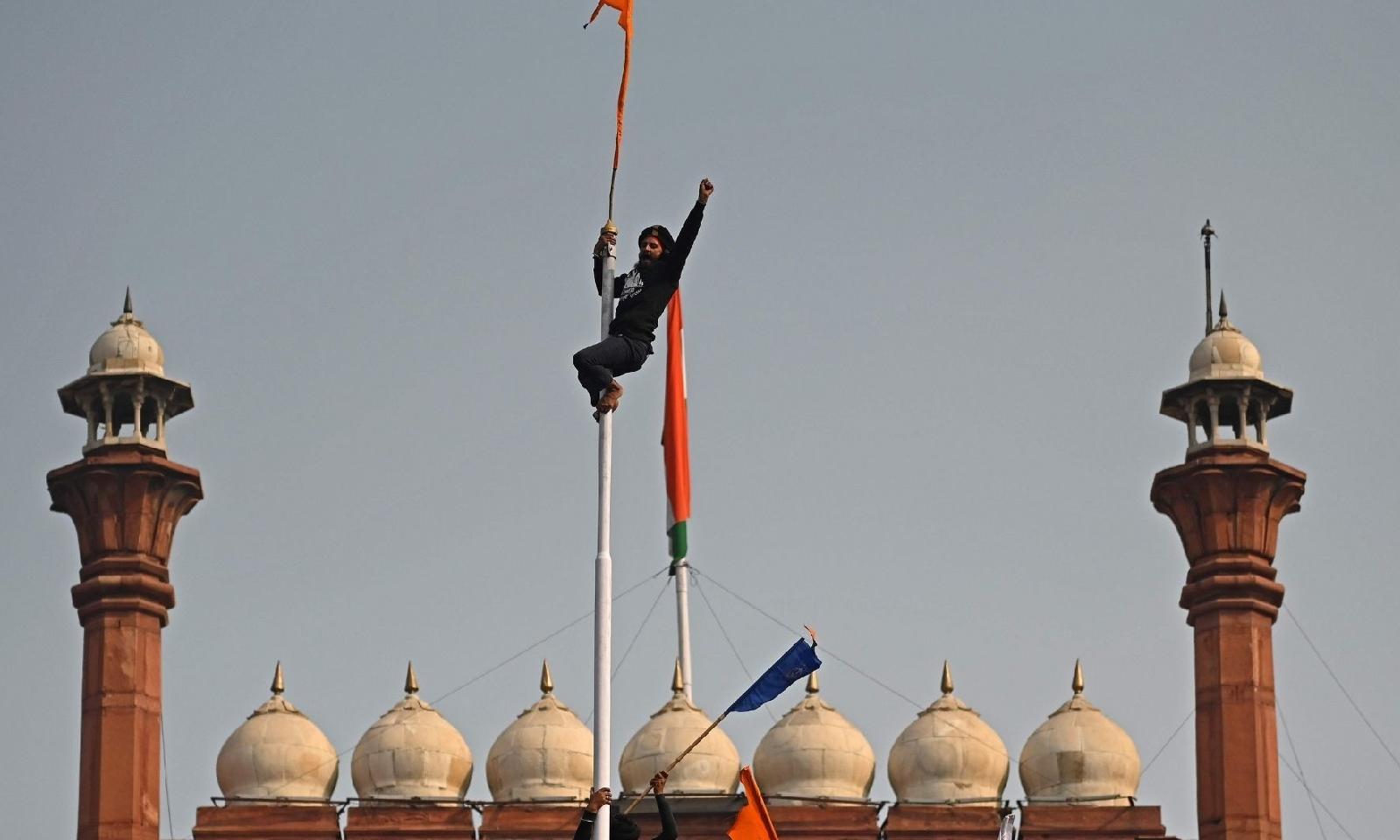 بھارتی کسانوں نے شدید احتجاج کرتے ہوئے لال قلعہ پر سکھوں کا مقدس جھنڈا لہرایا — فوٹو: اے ایف پی