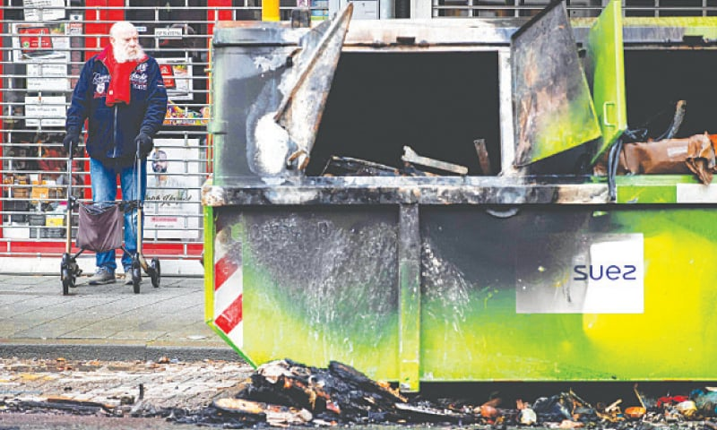 ROTTERDAM: A man stands near a damaged container on Tuesday after police clashed with rioters protesting against a curfew overnight.—AFP
