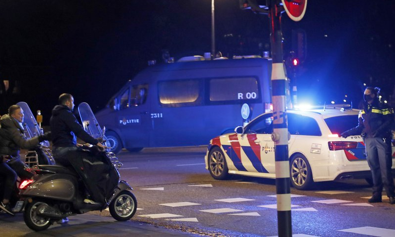 A police officer speaks to youths on scooters at a road block during a nation-wide curfew in Amsterdam, Netherlands on January 26. — AP