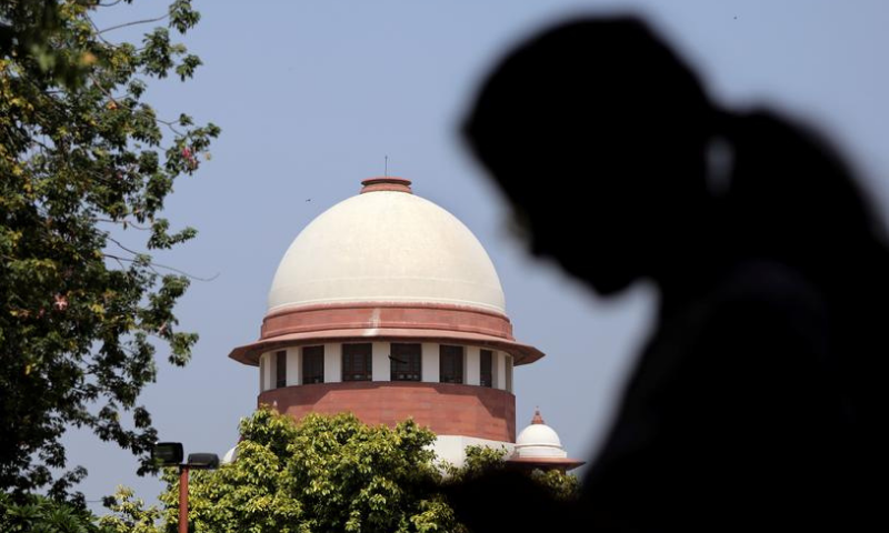 A woman checks her mobile phone inside the premises of the Supreme Court in New Delhi, India. — Reuters/File