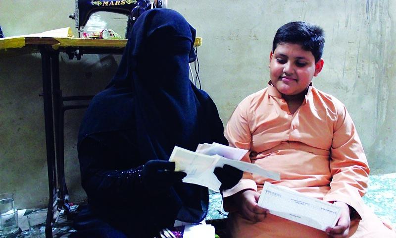 2013ء کی ایک تصویر جس میں احمد ربانی کی بیوی اور بیٹا جاوید ان کے بھیجے گئے خط پڑھ رہے ہیں—تصویر ذوفین ابراہیم